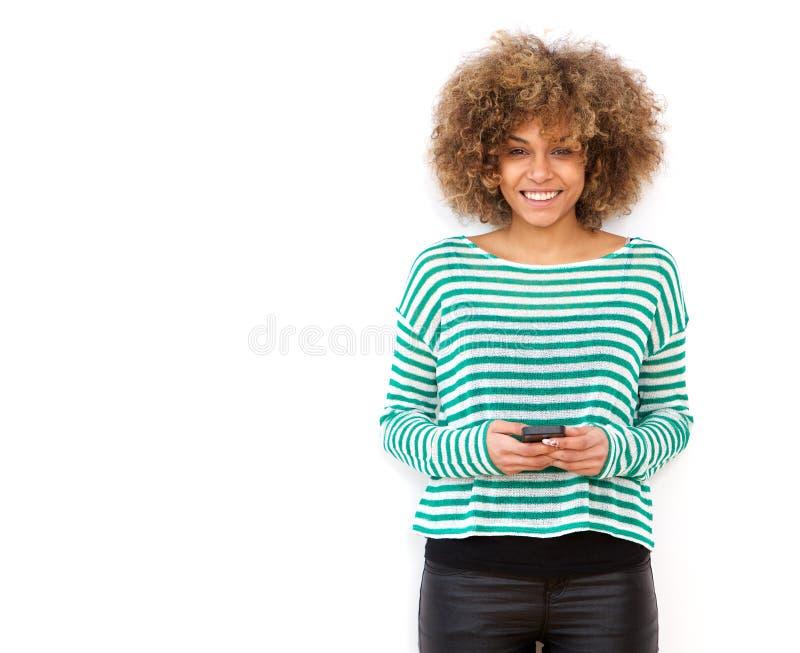 Lächelnde junge Afroamerikanerfrau, die Handy gegen weißen Hintergrund hält stockfotos