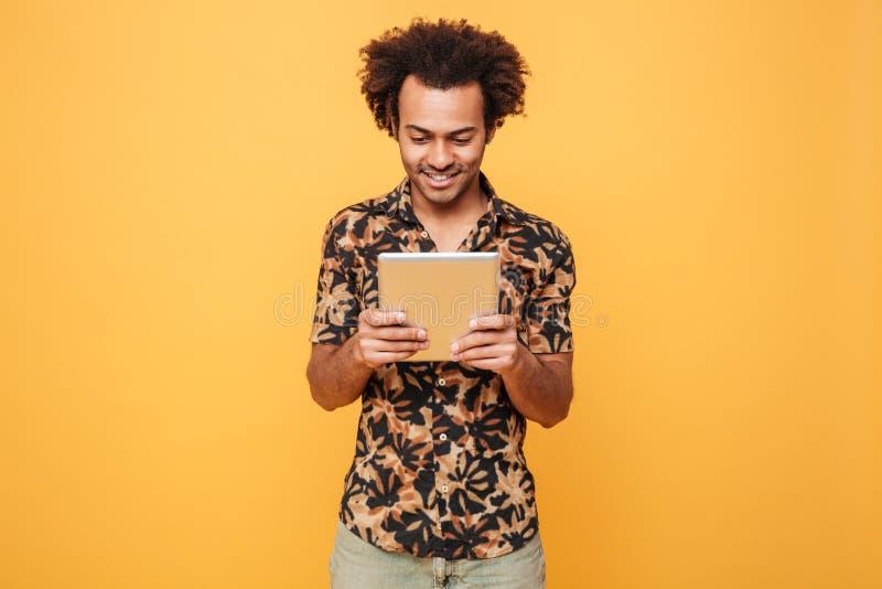 Lächelnde junge afroe-amerikanisch Kerlstellung und -anwendung der PC-Tablette stockfoto