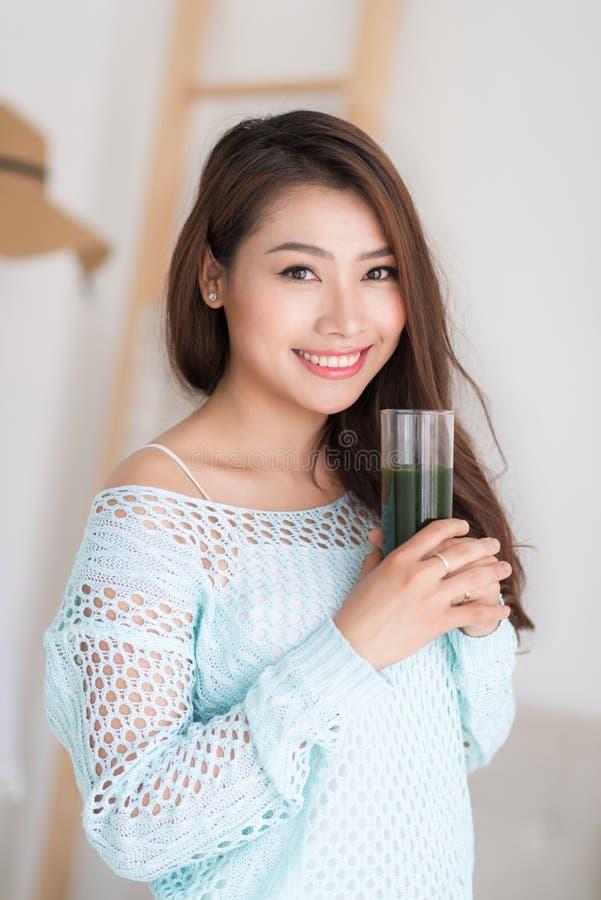 Lächelnde junge asiatische Frau, die grünen Frischgemüsesaft O trinkt lizenzfreie stockfotos