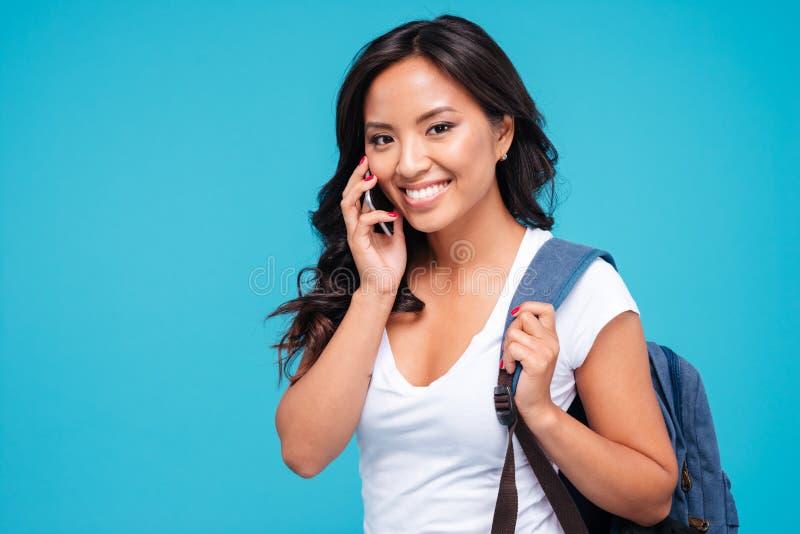 Lächelnde junge asiatische Frau mit Rucksack sprechend auf Mobiltelefon stockbild