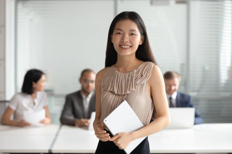 Lächelnde junge asiatische Geschäftsfrau, welche die digitale Tablette betrachtet Kamera hält stockbild