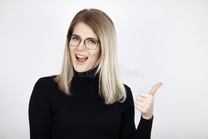 Lächelnde junge attraktive Blondine zeigt sich Daumen Gefühlporträt stockbild