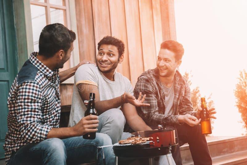 Lächelnde junge Bier trinkende und bei der Herstellung des Grills sprechende Freunde lizenzfreies stockbild