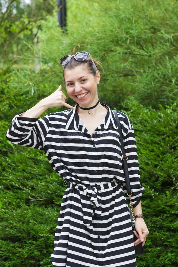 Lächelnde junge Brunettevertretung rufen mich Geste an lizenzfreies stockbild