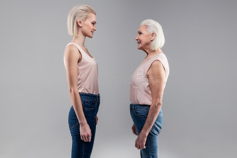 Lächelnde junge Dame der kurzhaarigen Blondine, die vor ihrem alten Selbst steht stockbilder