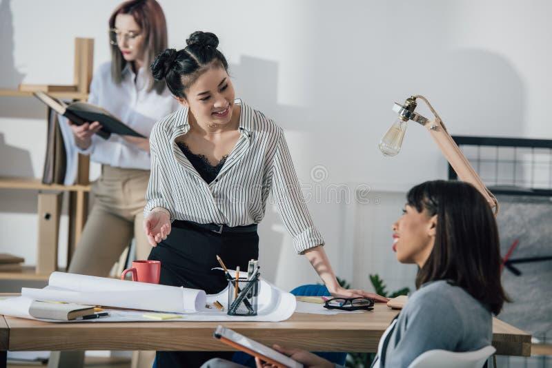 Lächelnde junge Designer, die mit Plan und digitaler Tablette im modernen Büro arbeiten stockfoto