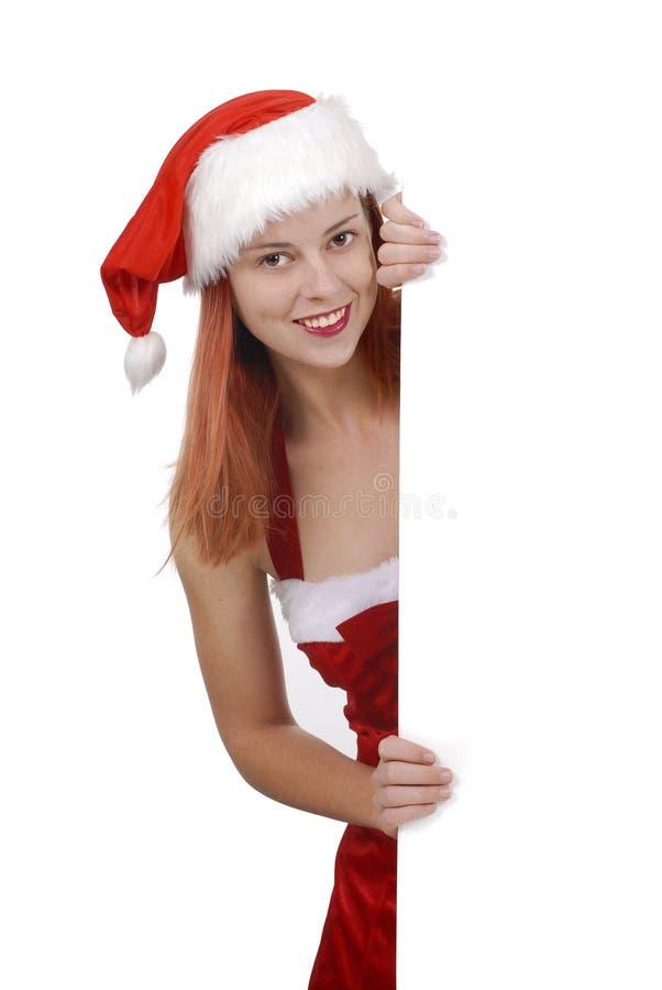 Lächelnde junge erwachsene Frau in Weihnachts-Sankt-Hut, der einfaches weißes leeres Brett oder Reklamefläche hält stockfotos