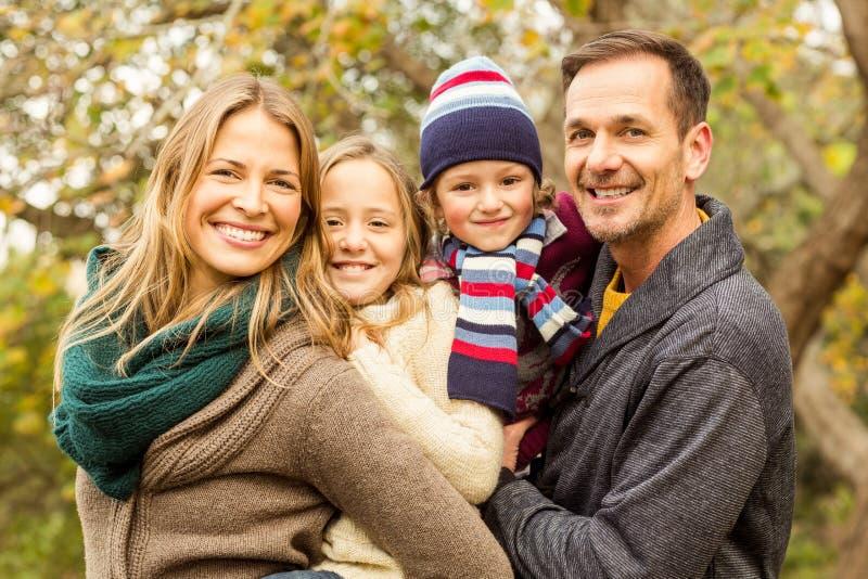 Lächelnde junge Familie, die zusammen aufwirft lizenzfreie stockbilder