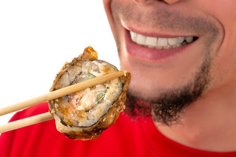 Lächelnde junge Fleisch fressende heiße Sushirolle lizenzfreie stockfotos