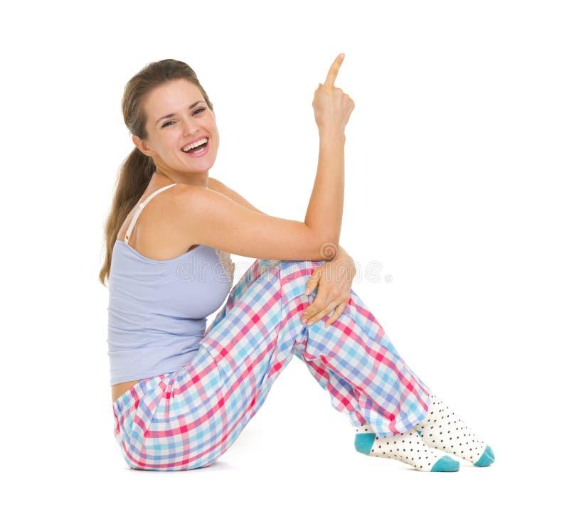 Lächelnde junge Frau in den Pyjamas, die auf Boden sitzen lizenzfreie stockbilder