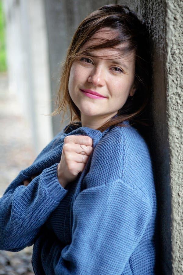 Lächelnde junge Frau des Brunette in der blauen Strickjacke stockbilder