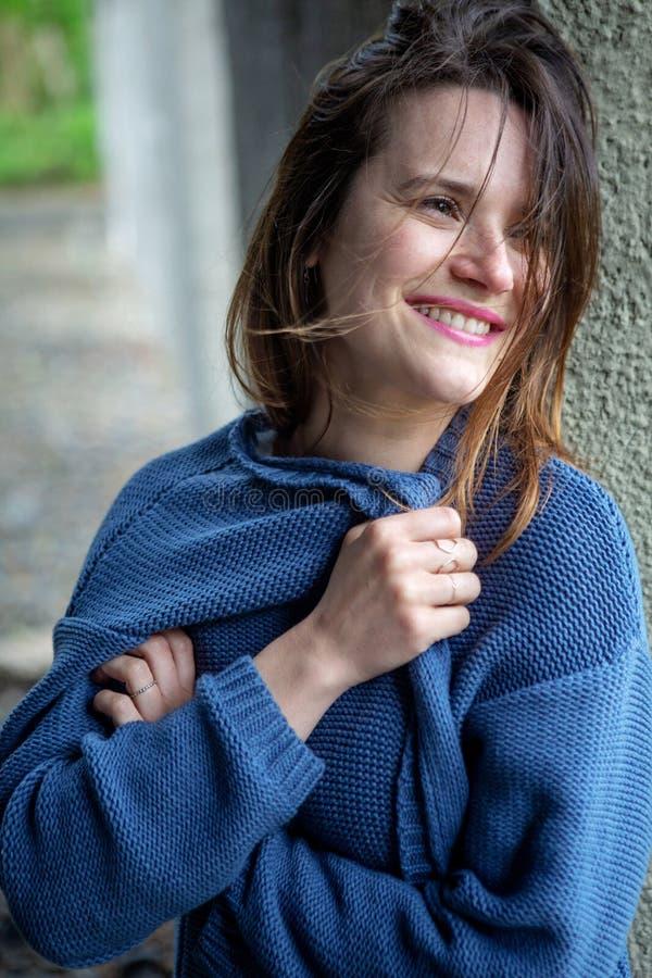 Lächelnde junge Frau des Brunette in der blauen Strickjacke stockfoto