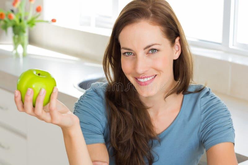 Lächelnde junge Frau, die Apfel in der Küche hält lizenzfreie stockbilder