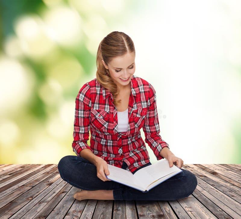 Lächelnde junge Frau, die auf Boden mit Buch sitzt stockfotografie