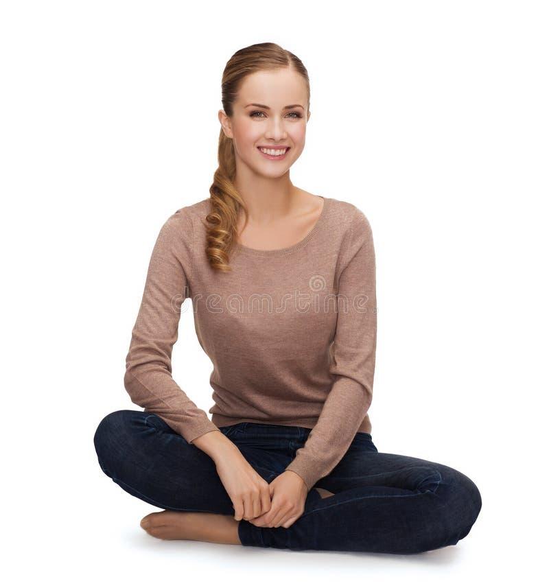 Lächelnde junge Frau, die auf Boden sitzt lizenzfreies stockfoto
