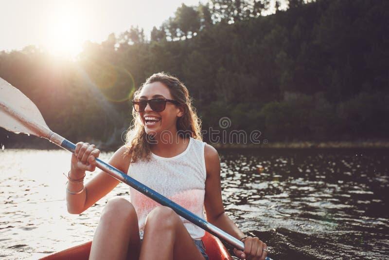 Lächelnde junge Frau, die auf einem See Kayak fährt stockfoto