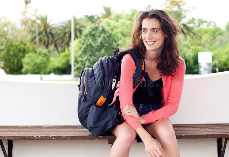 Lächelnde junge Frau, die auf einer Bank wartet mit Rucksack sitzt stockfoto