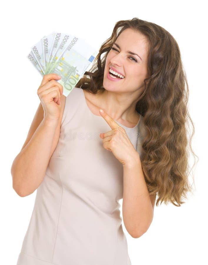 Lächelnde junge Frau, die auf Euros zeigt stockbild