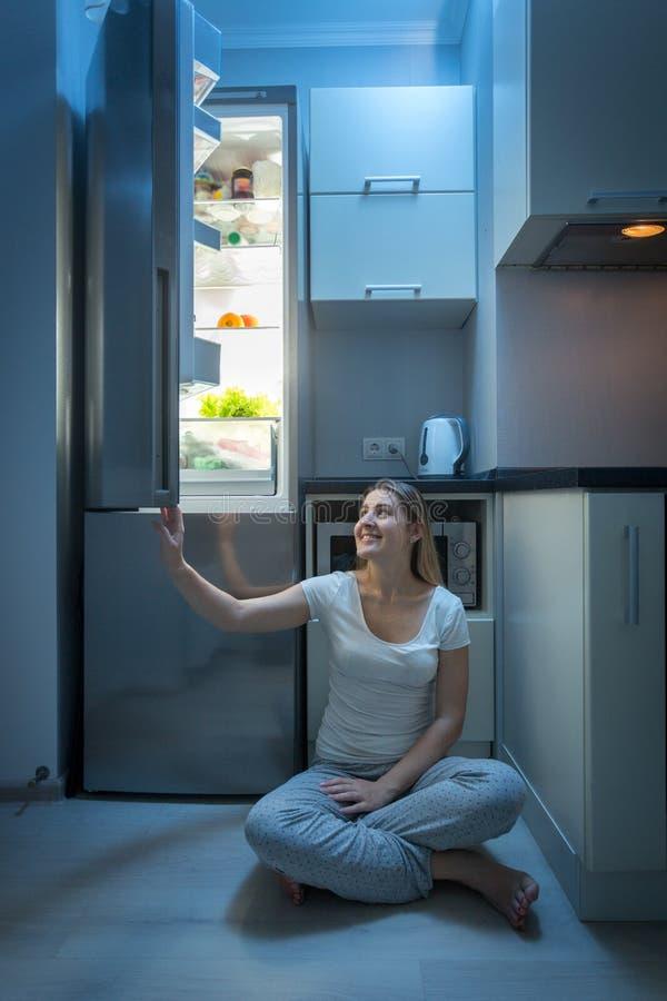 Lächelnde junge Frau, die auf Küchenboden an der Nacht und an öffnender Kühlschranktür sitzt stockfotos