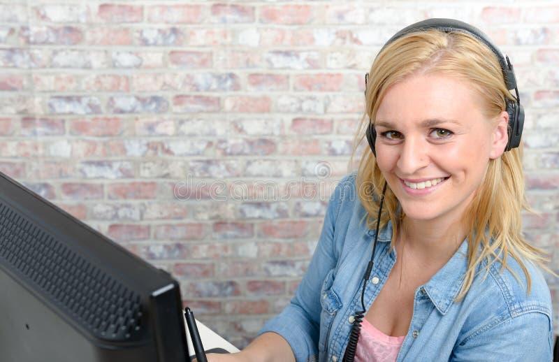 Lächelnde junge Frau, die an Computer arbeitet stockfotos