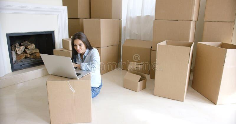 Lächelnde junge Frau, die an das Internet anschließt lizenzfreie stockbilder