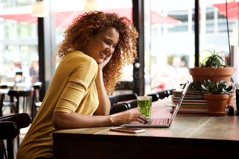 Lächelnde junge Frau, die an der Caféfunktion auf Laptop sitzt stockfotografie