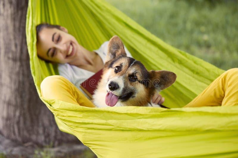 Lächelnde junge Frau, die draußen in der grünen Hängematte mit nettem Hund-Waliser-Corgi in einem Park stillsteht Schöne glücklic lizenzfreie stockfotos