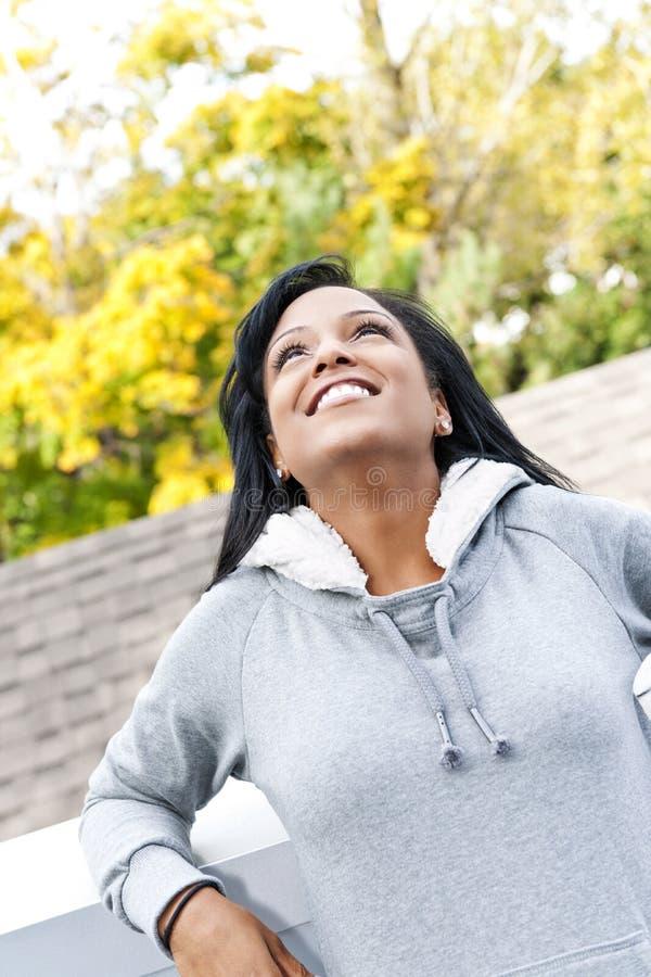 Lächelnde junge Frau, die draußen oben schaut stockfotografie