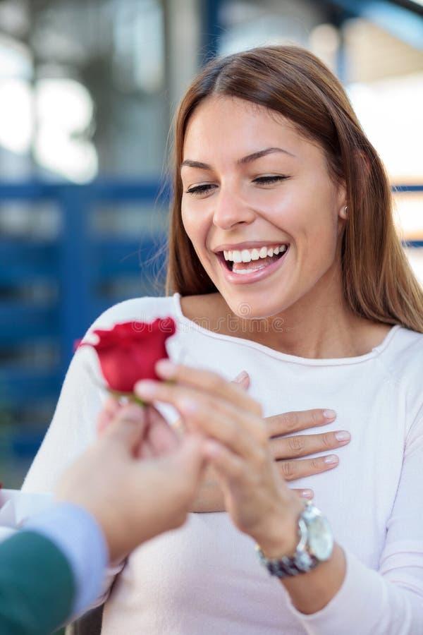 Lächelnde junge Frau, die eine einzelne rote Rose von ihrem Freund oder von Ehemann empfängt lizenzfreies stockfoto