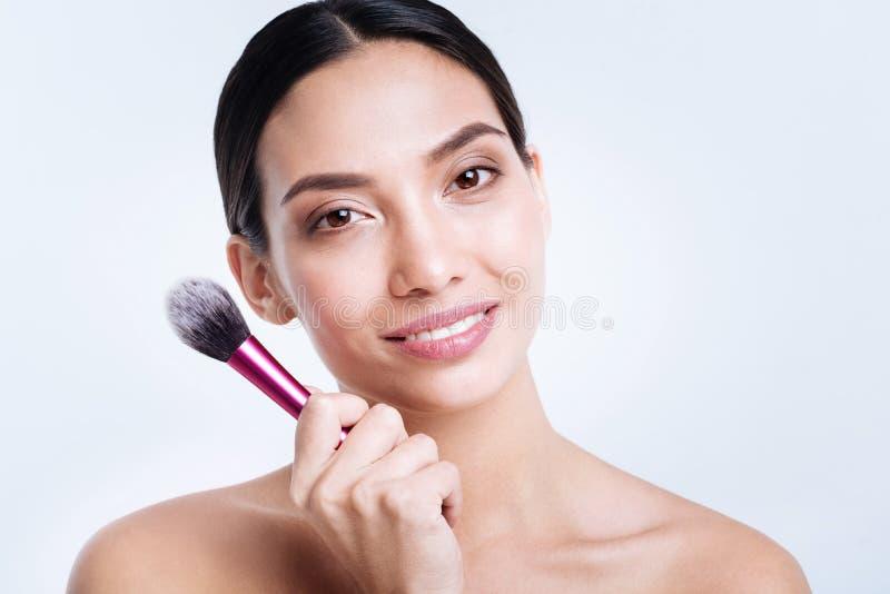 Lächelnde junge Frau, die eine Pulverbürste hält lizenzfreies stockfoto