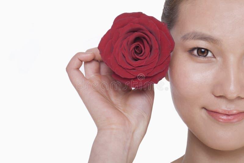 Lächelnde junge Frau, die eine rote Rose nahe bei ihrem Ohr, Atelieraufnahme hält lizenzfreie stockfotografie