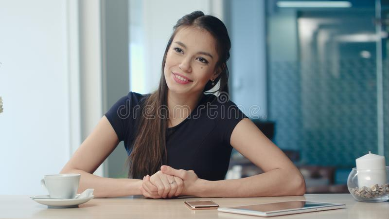 Lächelnde junge Frau, die einem Freund in einem Kaffeehaus Geschichte erzählt lizenzfreie stockfotos