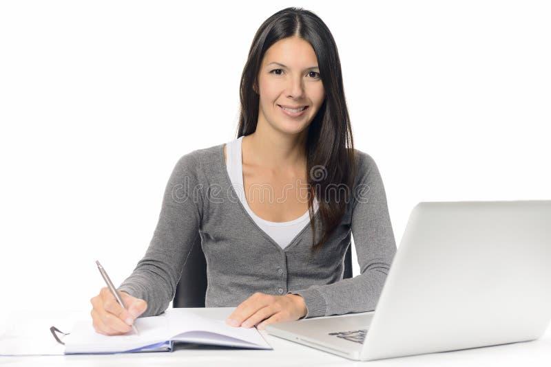 Lächelnde junge Frau, die an einem Schreibtisch arbeitet lizenzfreie stockfotos