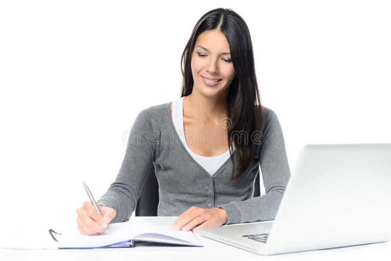 Lächelnde junge Frau, die an einem Schreibtisch arbeitet lizenzfreies stockfoto