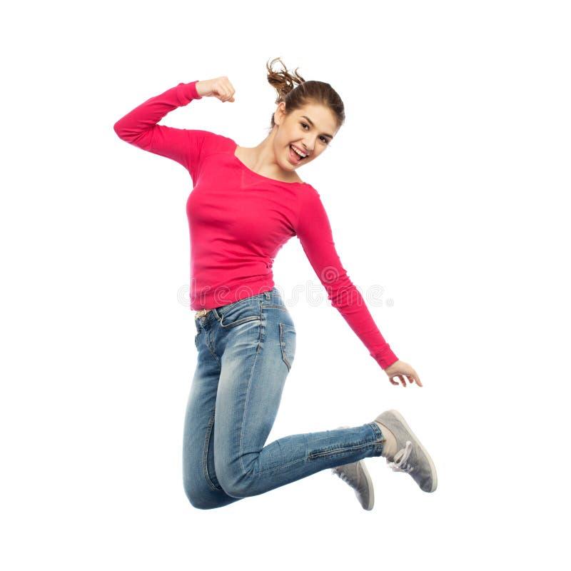 Lächelnde junge Frau, die in einer Luft springt stockbild