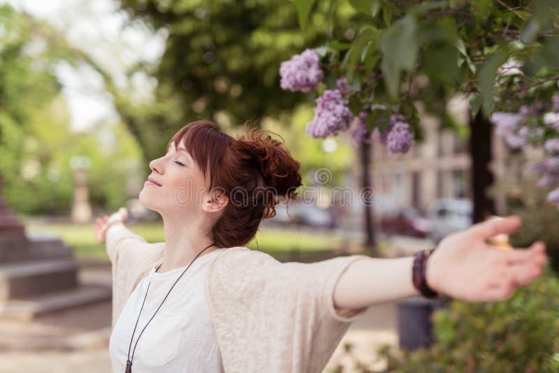 Lächelnde junge Frau, die Frühling feiert stockfotos