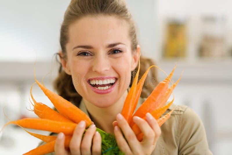 Lächelnde junge Frau, die frische Karotten zeigt lizenzfreie stockfotos