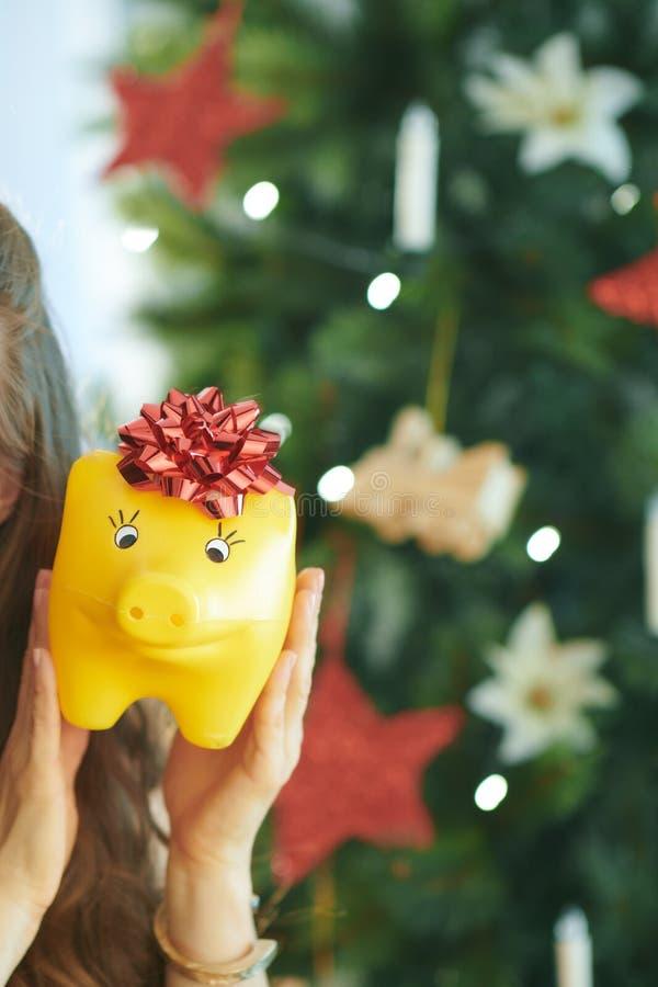 Lächelnde junge Frau, die gelbes Sparschwein mit rotem Bogen zeigt lizenzfreies stockfoto