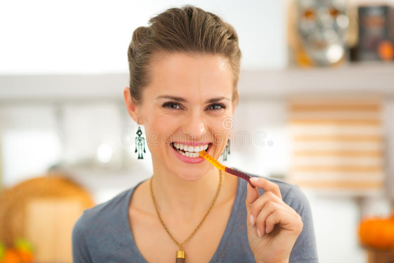 Lächelnde junge Frau, die gummiartige Wurmsüßigkeit Halloweens isst stockbild