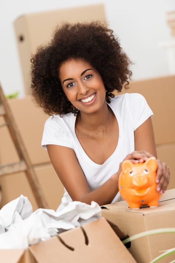 Lächelnde junge Frau, die ihr Sparschwein streichelt stockbild