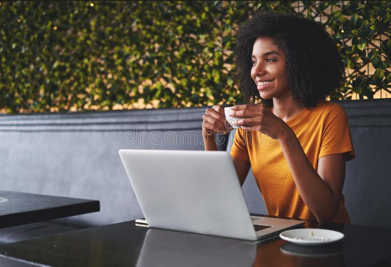 Lächelnde junge Frau, die im Café hält Kaffeetasse in der Hand sitzt lizenzfreies stockbild