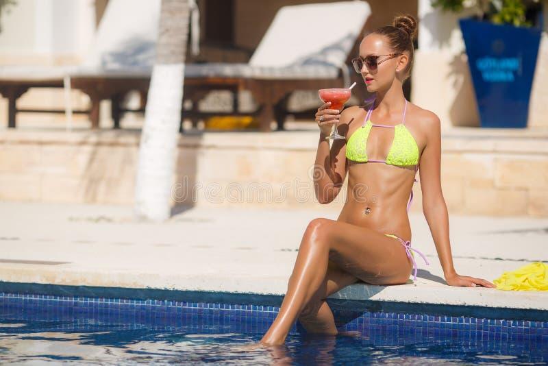 Lächelnde junge Frau, die im Pool mit Cocktail sich entspannt stockbilder