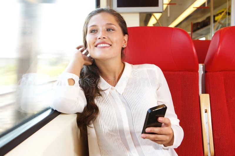 Lächelnde junge Frau, die im Zug unter Verwendung des Mobiltelefons sitzt stockfotografie