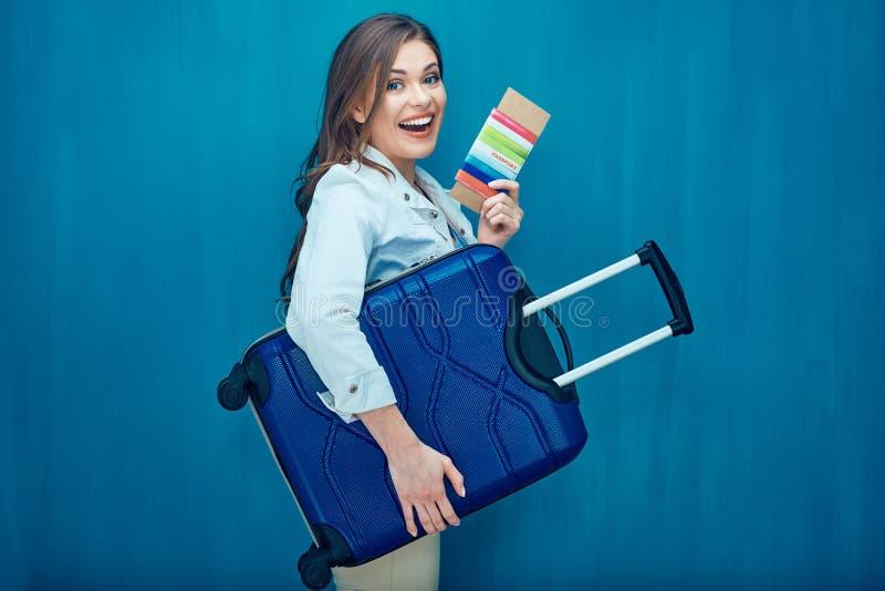 Lächelnde junge Frau, die Koffer, Pass, Karte hält stockfotos