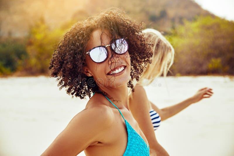 Lächelnde junge Frau, die mit einem Freund am Strand geht stockfoto