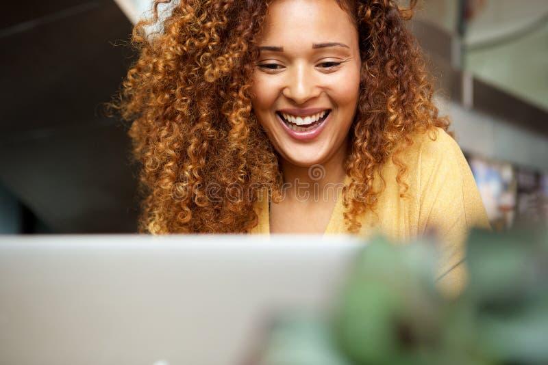 Lächelnde junge Frau, die mit Laptop arbeitet stockfoto