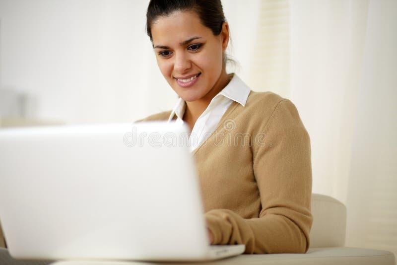 Lächelnde junge Frau, die mit Laptop-Computer arbeitet lizenzfreie stockfotografie
