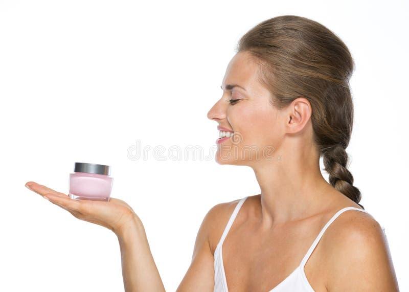 Lächelnde junge Frau, die Sahneflasche hält lizenzfreies stockfoto