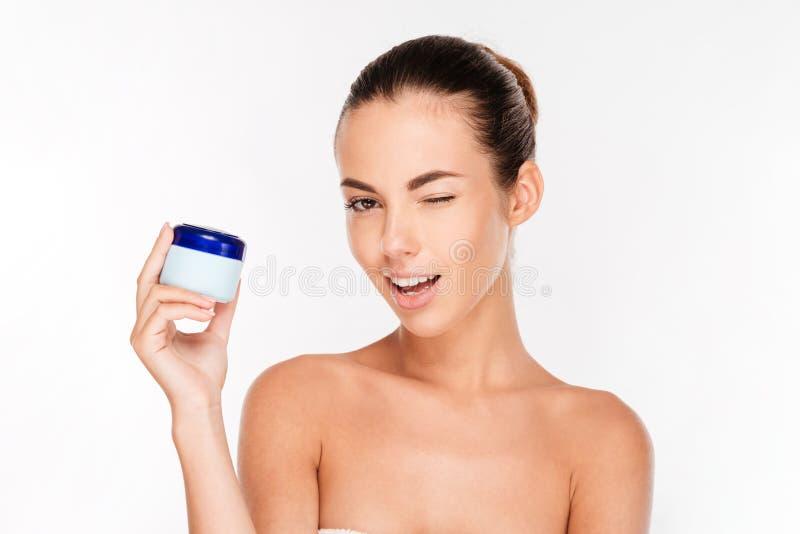 Lächelnde junge Frau, die Sahneflasche und das Blinzeln hält stockfoto