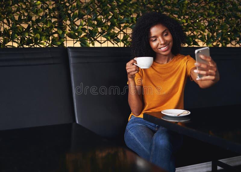 Lächelnde junge Frau, die selfie am Handy nimmt stockfotos
